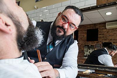 Barber cutting man's beard - p300m1205826 by Andrés Benitez