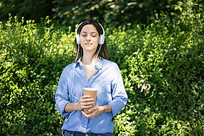 Woman with headphones listening music in nature - p300m2070700 by Robijn Page