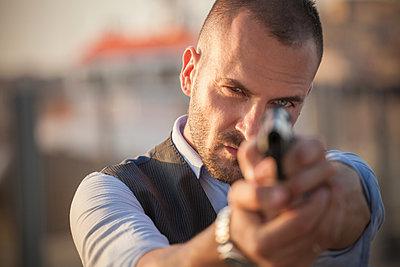Close up of man poised with handgun looking at camera - p429m1174924 by ROBERTO PERI