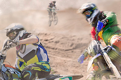 Three young male motocross riders racing on dusty track - p429m983033f by Zero Creatives