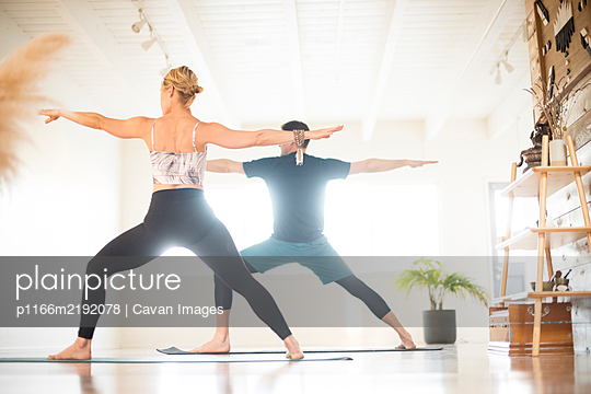 A couple in warrior 2 pose during yoga. - p1166m2192078 by Cavan Images