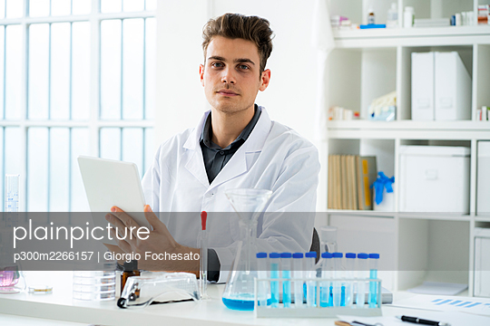 Young male scientist holding digital tablet while sitting at desk in laboratory - p300m2266157 by Giorgio Fochesato