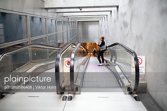 Woman on moving walkway - p312m2086408 by Viktor Holm