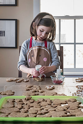Cute girl putting ingredient on gingerbread man at home - p1166m2025144 by Cavan Images