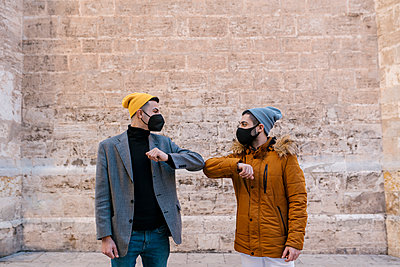 Young men wearing knit hat and protective face mask giving elbow bump while greeting against wall - p300m2251093 by Ezequiel Giménez