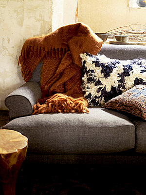 Woollen blanket and cushions on sunlit grey sofa - p349m2167830 by Polly Wreford