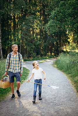 Smiling daughter talking to father holding picnic basket on road in forest - p426m2213189 by Maskot
