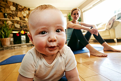 Baby crawling on floor while mother rests from workout - p555m1305271 by Peathegee Inc