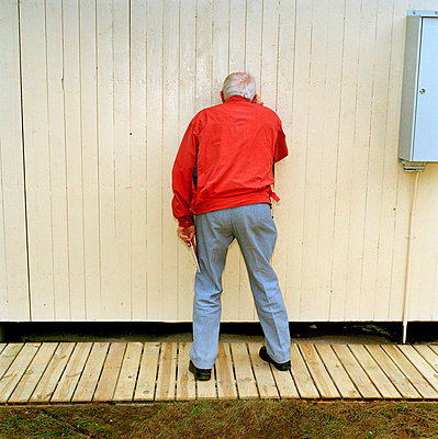 Senior adult spying by wooden wall - p8474587 by Urban Jörén