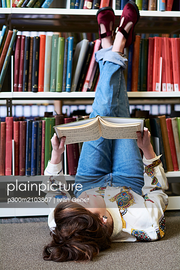 Female student reading book in a public library - p300m2103807 by Ivan Gener