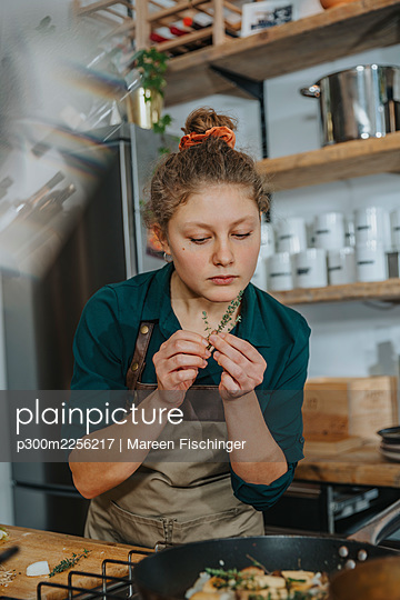 Young chef smelling thyme leaf while standing in kitchen - p300m2256217 by Mareen Fischinger