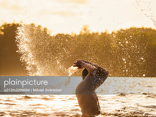 Boy in sea splashing water - p312m2299684 by Mikael Svensson