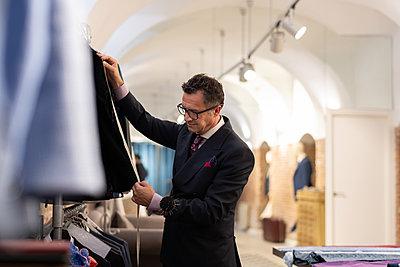 Senior tailor doing jacket measurements - p1166m2261422 by Cavan Images