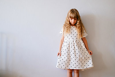 Blonde girl in a polka dot dress standing by a wall - p1414m2044848 by Dasha Pears