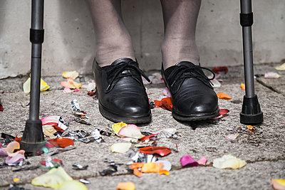 Schuhe einer alten Frau, Krücken, Blütenblätter, Konfetti - p1685m2272477 von Joy Kröger