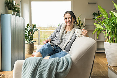 Portrait of happy woman with a mug and tablet sitting on the couch at home - p300m2104573 by Uwe Umstätter