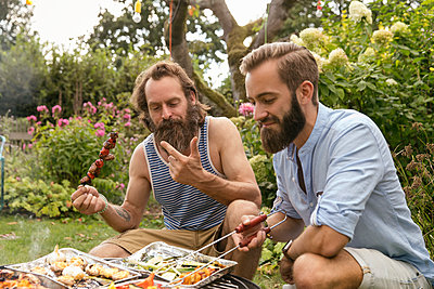 Two men at the barbeque in the garden - p788m2027464 by Lisa Krechting