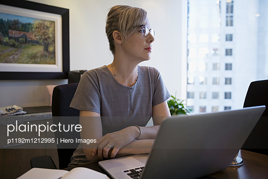 Pensive female lawyer looking away at laptop