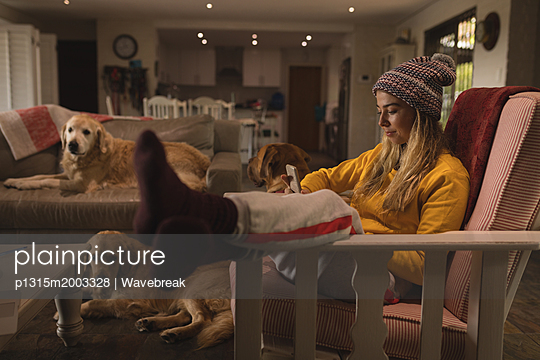 Girl with dogs using mobile phone in living room at home - p1315m2003328 by Wavebreak