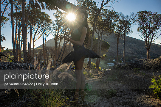 Woman in ballet skirt on tiptoes at sunset - p1640m2264322 by Holly & John