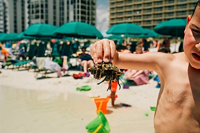 Brave boy holding crab while standing on Florida beach - p1166m2094948 by Cavan Images