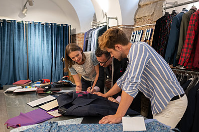 Client discussing sketch with dressmaker and assistant - p1166m2261439 by Cavan Images