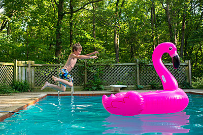 Boy playing with flamingo floating device - p1169m2108500 by Tytia Habing