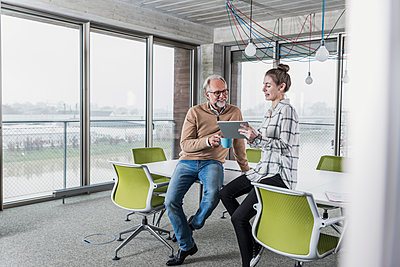 Casual mature businessman and young woman with tablet in conference room in office - p300m1562458 by Uwe Umstätter