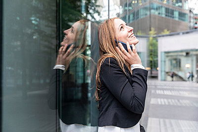 Smiling businesswoman on the phone in the city - p300m2156856 by William Perugini