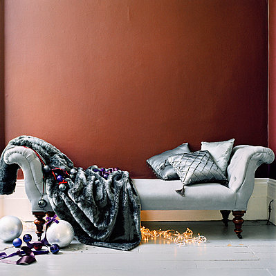 Upholstered sofa with cushions and blanket and Christmas decorations - p349m695156 by Emma Lee