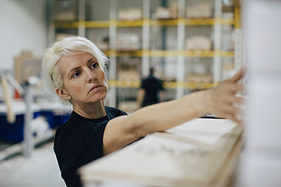 Serious woman examining wooden planks in industry - p426m1537064 by Maskot