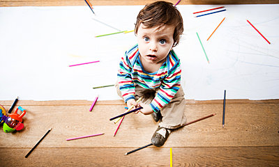 Overhead view of male toddler sitting on floor with coloured pencils and long paper - p429m1418481 by Bonfanti Diego