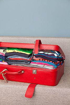 Red suitcase cram-full - p4540876 by Lubitz + Dorner