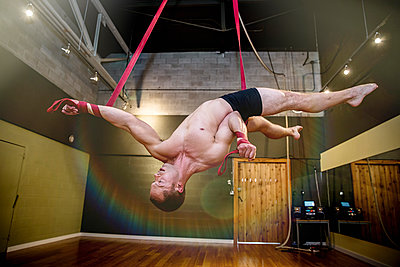 Caucasian acrobat hanging from ropes in studio - p555m1412621 by Inti St Clair