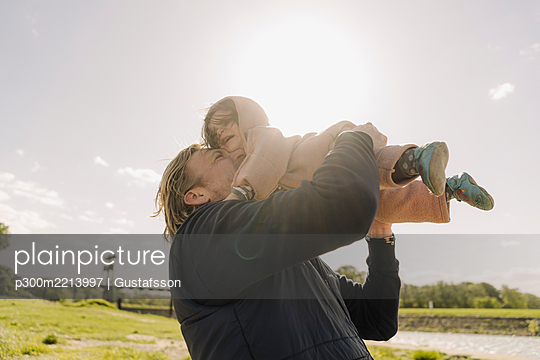 Cheerful father nuzzling daughter while lifting her in air on sunny day - p300m2213997 by Gustafsson