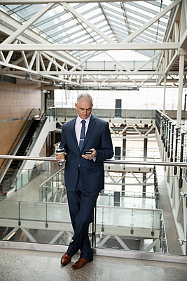 Businessman with coffee using smart phone on office atrium balcony - p1192m2093720 by Hero Images
