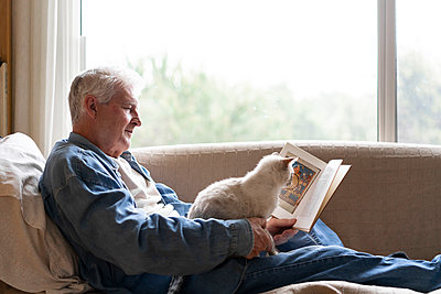 Senior man reading book while sitting with cat on sofa by window at home - p300m2197269 by VITTA GALLERY