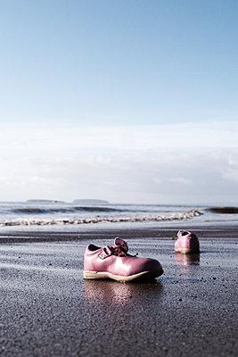 Rosa Kinderschuhe am Strand - p597m1161390 von Tim Robinson