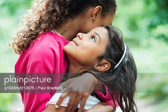 Close up affectionate cute sisters hugging - p1023m2213076 by Paul Bradbury
