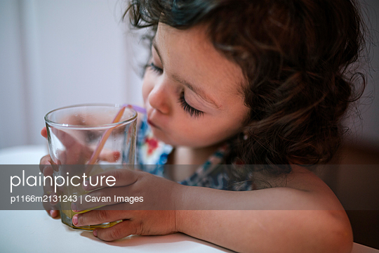 Adorable little girl drinking an orange juice - p1166m2131243 by Cavan Images