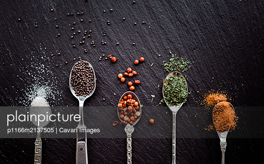 A selection of spices on vintage spoons on a slate chopping board - p1166m2137505 by Cavan Images
