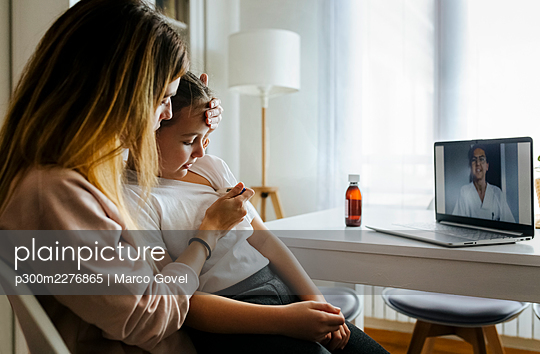 Woman checking fever through thermometer with pediatrician on video call over laptop at home - p300m2276865 by Marco Govel