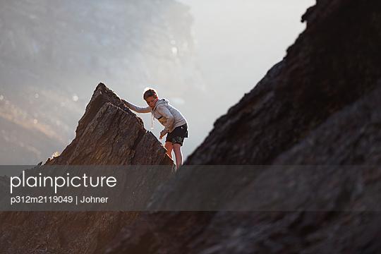Boy climbing mountain - p312m2119049 by Johner