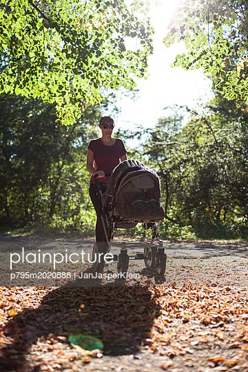 Frau mit Kinderwagen im Park - p795m2020888 von Janklein