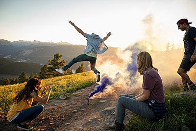 Playful friends enjoying colorful smoke bomb on sunny mountain hilltop, Alberta, Canada - p1192m2016562 by Hero Images