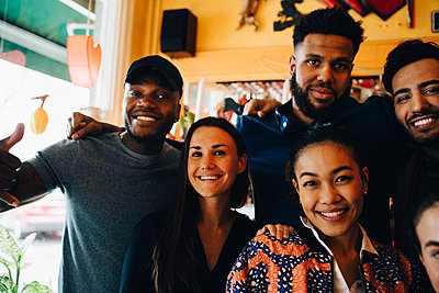 Portrait of smiling young multi-ethnic friends while standing in restaurant during brunch - p426m2046276 by Maskot