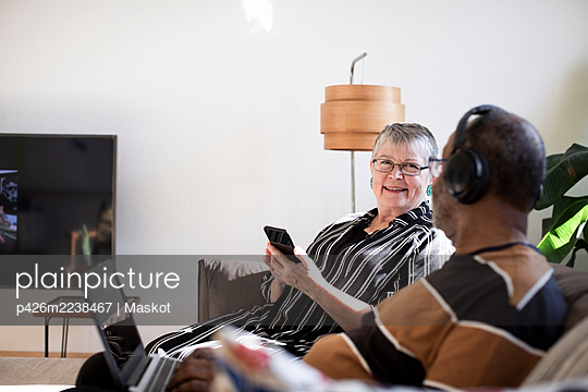 Senior couple with smart and laptop sitting on sofa in living room - p426m2238467 by Maskot