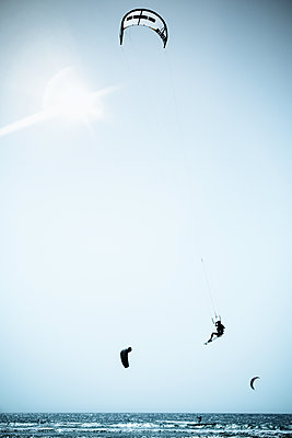 Kite surfer jumps over the sea - p1053m2115343 by Joern Rynio