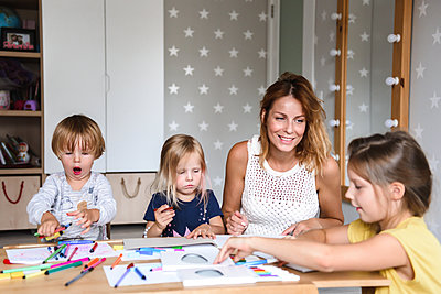 Mom with young children drawing with felt-tip pens - p1166m2159622 by Cavan Images