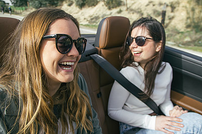 Two women with sunglasses laughing in a convertible car - p300m1120632f by Andrés Benitez